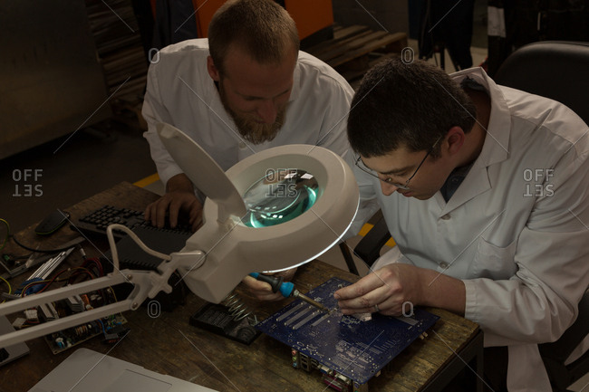 Robotics engineers assembling circuit board at desk in warehouse
