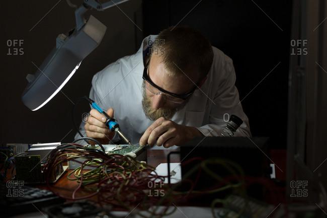Robotics engineer assembling circuit board at desk in warehouse