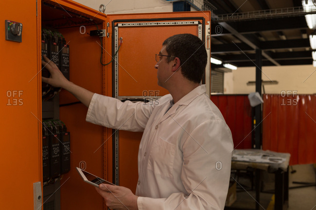 Robotics engineer examining control panel in warehouse