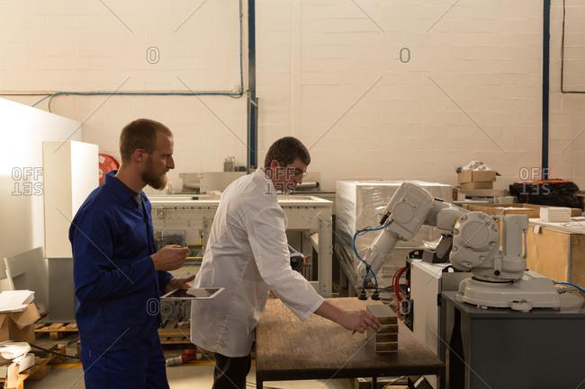 Robotic engineers testing robotic machine in warehouse