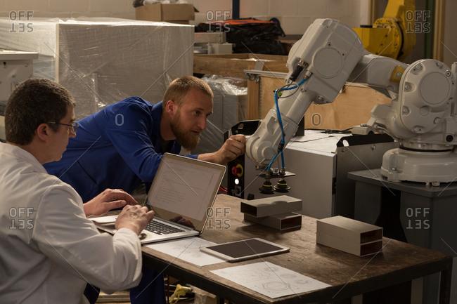 Robotic engineers examining robotic machine in warehouse