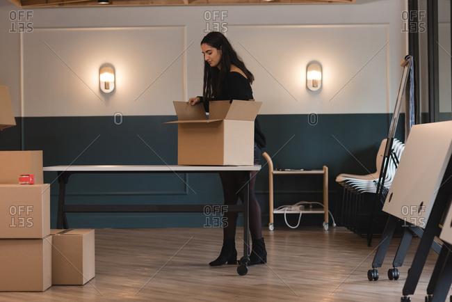 Businesswoman unboxing cardboard box in office
