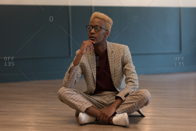 Thoughtful businessman sitting on floor in office