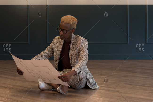 Smart businessman holding blueprint in office