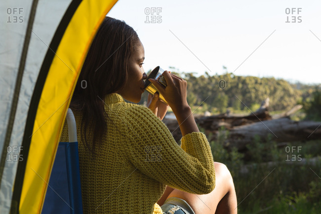Woman having coffee near tent in the forest