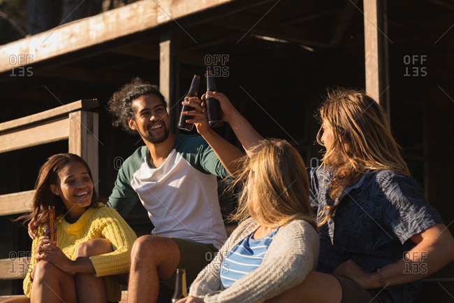 Happy group of friends toasting beer bottle on cabin