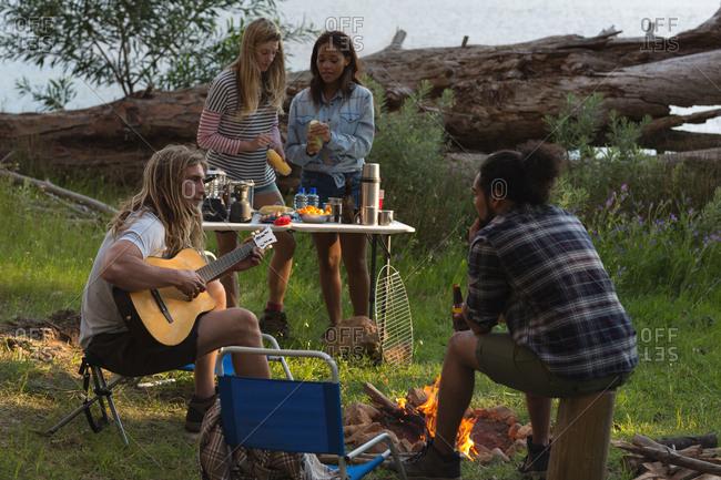 Group of friends having fun near bonfire at campsite