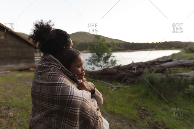 Romantic couple wrapped in blanket at campsite