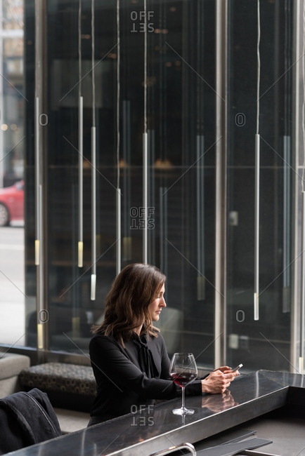 Businesswoman having red wine while using mobile phone in hotel