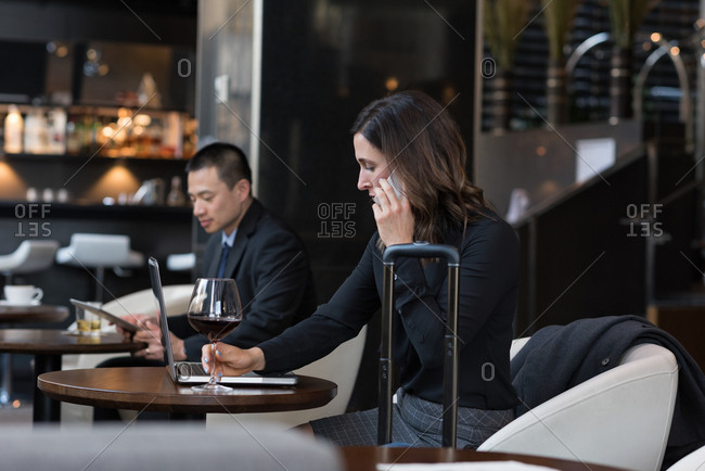 Businesswoman having red wine while talking on mobile phone in hotel