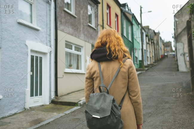 Rear view of redhead woman standing on alley street