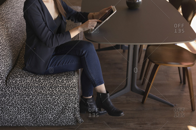 Businesswoman using digital tablet in cafeteria at office