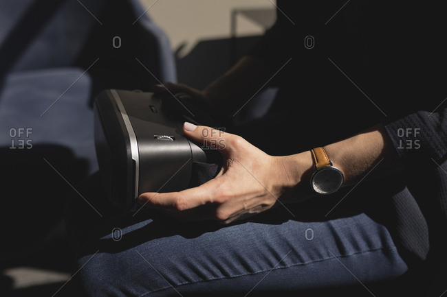 Mid section of businesswoman holding virtual reality headset in office