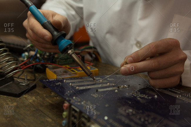 Close-up of robotics engineer assembling circuit board at desk
