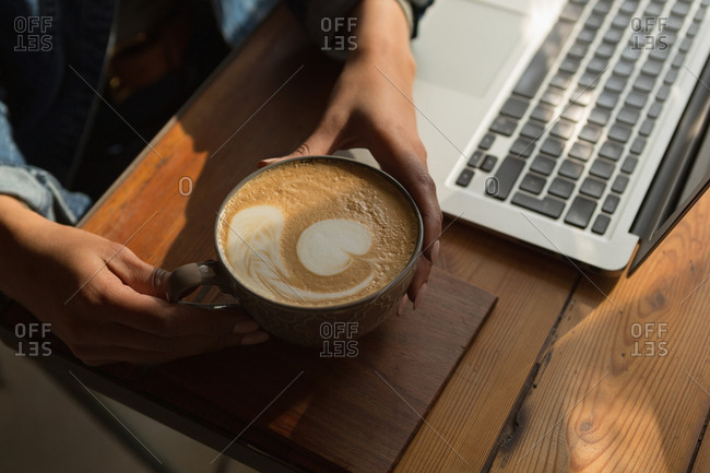 Close-up of woman holding coffee cup in cafe