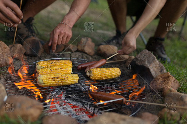 Close-up of men roasting sausage and corn on campfire at campsite