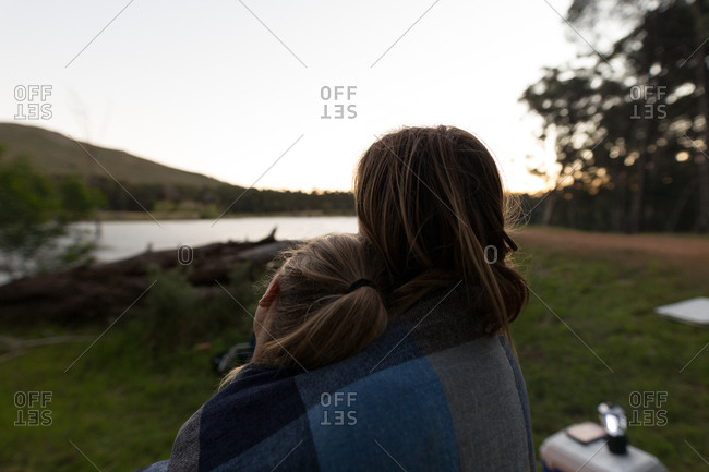 Rear view of couple wrapped in blanket at campsite