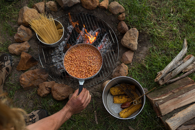 Food being prepared on bonfire at campsite