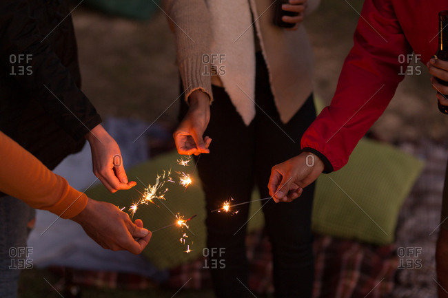 Mid section of group of friends having fun with sparklers