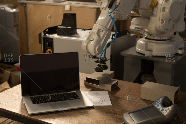 Laptop, robotic machine and remote control on table in warehouse