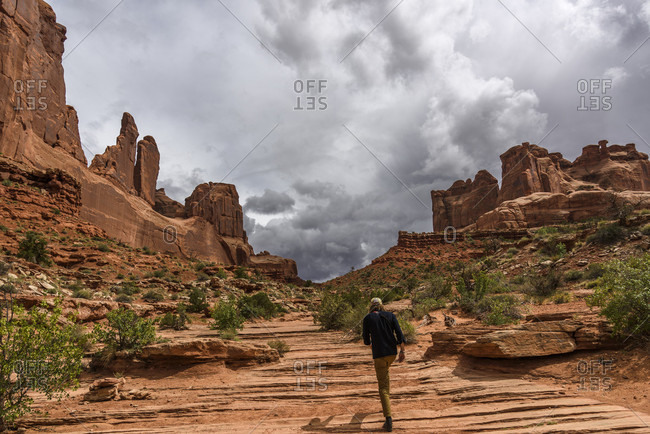 Rear view of man hiking in Park Avenue, Arches National Park, Utah, USA