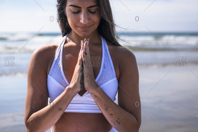 Front view shot of young woman with black hair and hands clasped doing yoga on beach