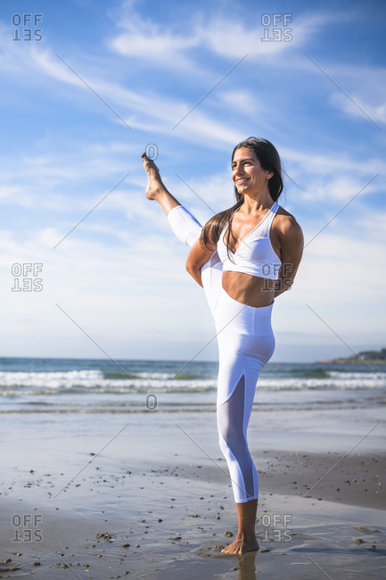 Young woman with black hair standing on one leg while doing yoga on beach