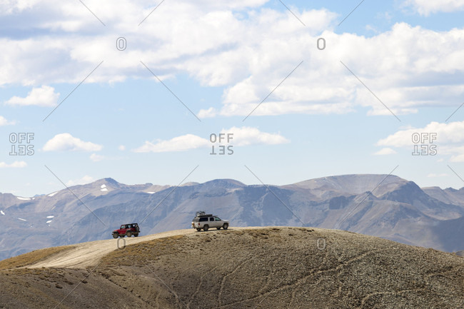 Distant view of two 4x4 cars on dirt road on hill, Alpine Loop, Colorado, USA