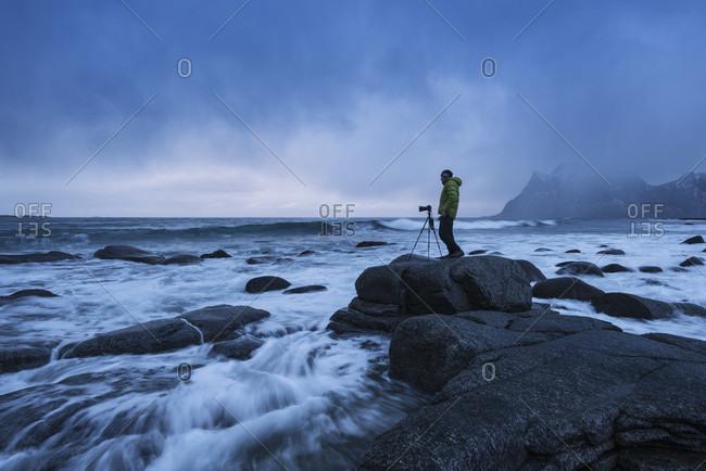 Side view shot of photographer with tripod standing on rocky seashore, Uttakleiv beach, Vestvagoya, Lofoten, Norway