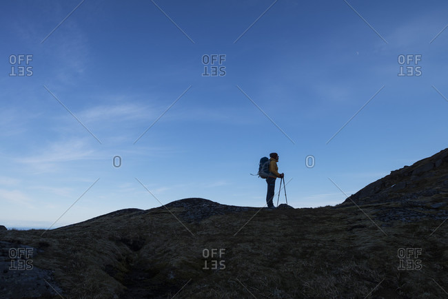 Side view of single female hiker standing on mountain ridge, Moskenesoya, Lofoten Islands, Norway