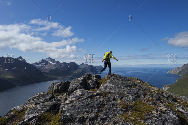 Rear view shot of female hiker on summit of Riven with Oyfjord in background, Senja, Troms, Norway