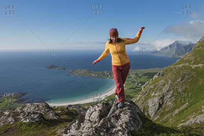 Front view shot of female hiker balancing while walking across rocks on summit of Nubben, Ramberg, Flakstadoya, Lofoten Islands, Norway