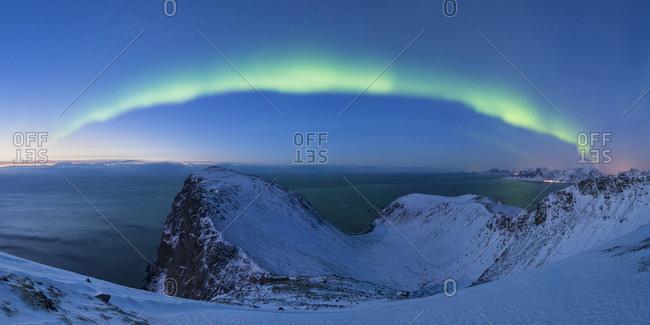 Beautiful landscape with aurora borealis over summit of Ryten, Moskenesoya, Lofoten Islands, Norway