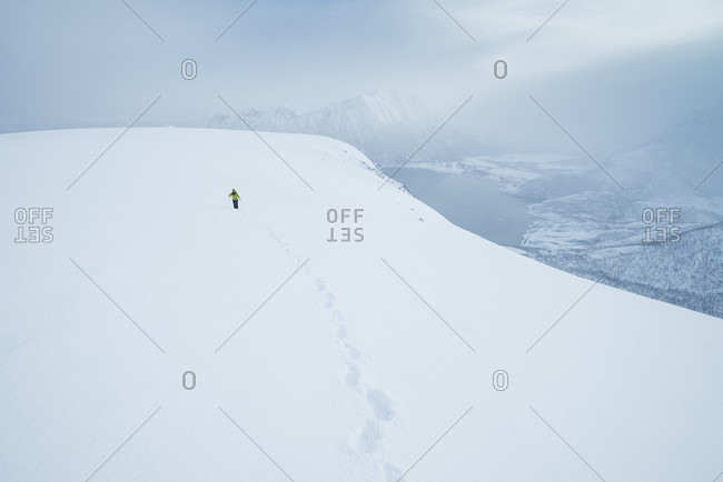 Distant view of hiker in winter ascending Matmora mountain peak, Austvagoy, Lofoten Islands, Norway