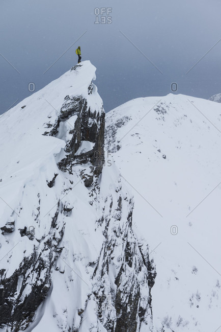 Distant view shot of single female hiker on ridge in winter while ascending Matmora mountain peak, Austvagoy, Lofoten Islands, Norway
