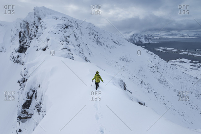 Distant view of single female hiker ascending Matmora mountain peak in winter, Austvagoy, Lofoten Islands, Norway