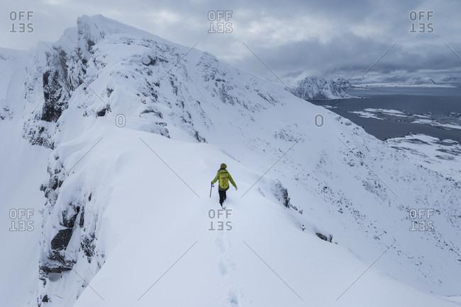 Distant view of single female hiker ascending Matmora mountain peak in winter, Austvagoy, Lofoten Islands, Norway