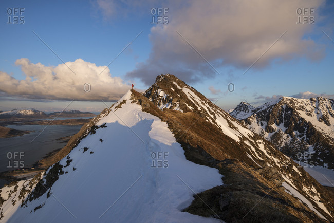 Distant view shot of single hiker on narrow summit ridge of Slettind mountain peak, Flakstadoya, Lofoten Islands, Norway
