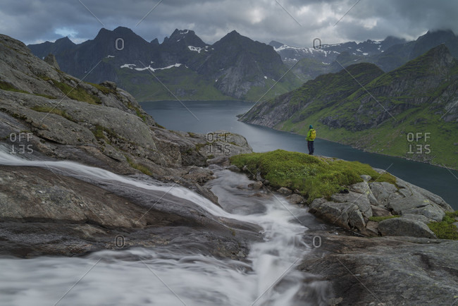 Distant view of hiker standing near waterfall at Kirkefjord, Moskenesoya, Lofoten, Norway
