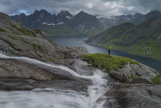 Distant view of hiker standing near waterfall at Kirkefjord, Moskenesoya, Lofoten, Norway