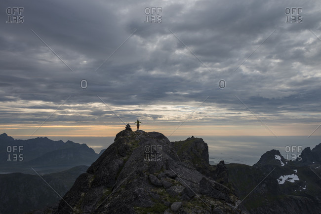 Distant view of female hiker on summit of Stjerntind at sunset, highest peak of Flakstad community, Flakstadoya, Lofoten Islands, Norway