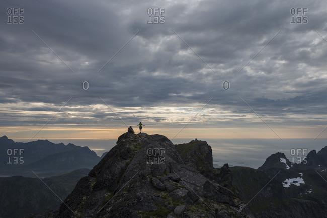 Distant view of female hiker on summit of Stjerntind at sunset, highest peak of Flakstad community, Flakstadoya, Lofoten Islands, Norway