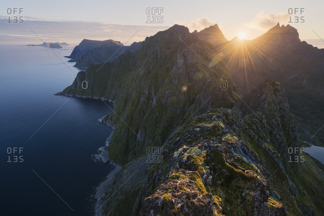 Majestic natural scenery with aerial view of coastal mountains under shining sun at sunset, Moskenesoya, Lofoten, Norway