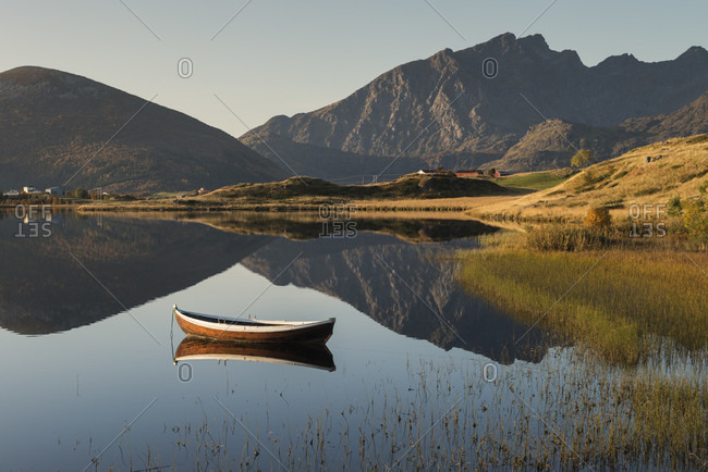 Tranquil scenery with rowboat and reflections of mountains in lake, Vestvagoya, Lofoten, Norway