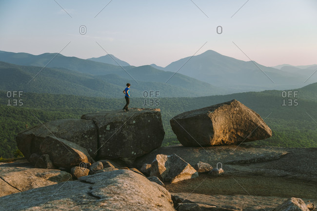 Distant view of woman standing on boulder while hiking, Pitchoff Mountain, Adirondack Mountains, New York State, USA