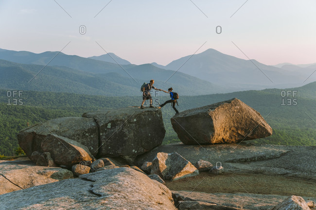 Distant view of man helping woman across boulder while hiking, Pitchoff Mountain, Adirondack Mountains, New York State, USA