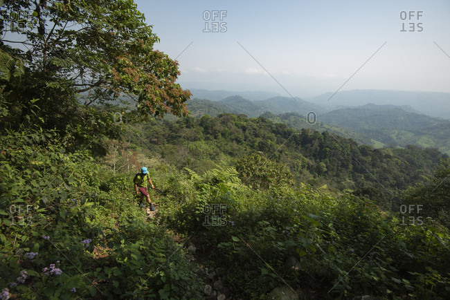 One man hikes on a trail at the area of Los Limones in Xicotepec de Juarez, Puebla, Mexico.