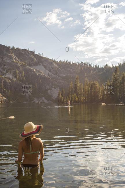 Rear view of woman in bikini and with sun hat standing in lake, Shasta, California, USA