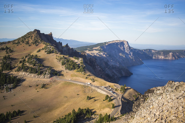 View looking down on a mountain road curving along an exposed ridgeline above a deep blue lake, Crater Lake, Oregon, USA