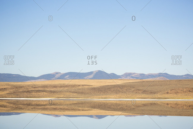A landscape photograph of glass-calm Abert lake in an arid background under blue sky, Oregon, USA